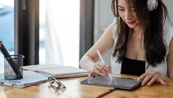 Cerca de una joven empresaria en el lugar de trabajo con su tableta digital foto
