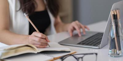 Close up of Asian woman writing on notebook on a table with laptop, girl work at a coffee shop, freelance business concept photo