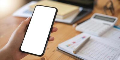 Mockup image of a person holding a cell phone with a blank white screen for text photo