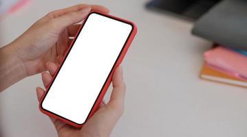 mujer sosteniendo un teléfono inteligente con una maqueta de pantalla blanca foto