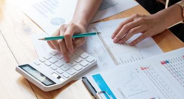 Close up businesswoman using calculator and laptop for doing math finance on wooden desk in office and business working background, tax, accounting, statistics, and analytic research concept photo