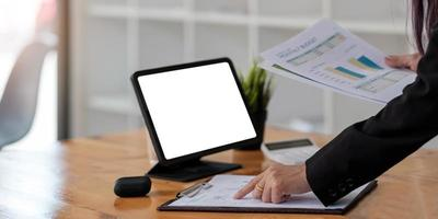 Businesswoman points on papers and holding papers preparing a report photo