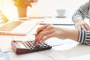 Businesswoman using a calculator and writing notes. Taxes, savings, finances, and economy concept photo