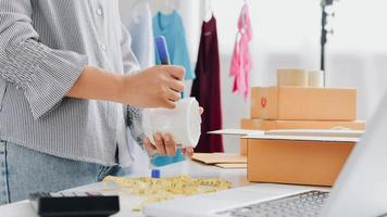 Closeup view of female's online store, small business owner seller, entrepreneur packing package, post shipping box preparing delivery parcel on the table, entrepreneurial self-employed business concept photo