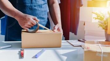 Close-up view of man's online store, small business owner seller, entrepreneur packing package post shipping box preparing delivery parcel on the table, entrepreneurial self-employed business concept photo