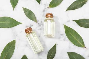 Aceite esencial de laurel de bahía en mesa de mármol foto