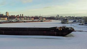 Old ship barge on a frozen river aerial shooting video