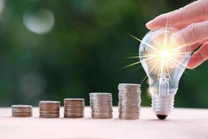Businessman hand holding light bulb with money coins photo