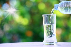 Water flows into a glass on table and mineral water health care concept photo
