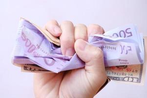 sosteniendo el dinero del billete y ahorrando dinero y el concepto de crecimiento empresarial foto