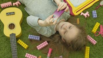 little girl lying on a green background in headphones and using a phone top view video