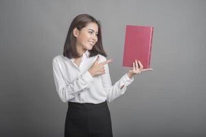 Hermosa mujer maestra sosteniendo un libro sobre fondo gris foto