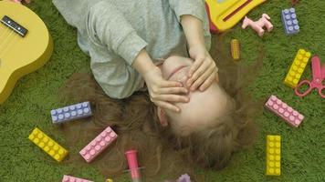 little girl laughs lying on green background top view video