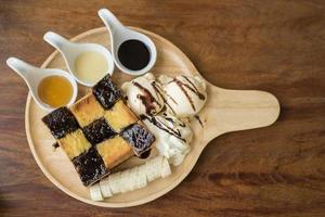 Honey toast with vanilla ice cream, whipped cream and chocolate syrup. Served with banana photo