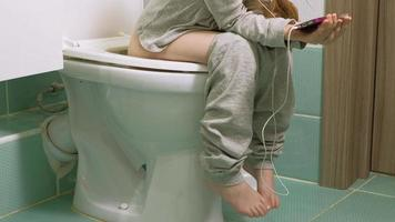 menina senta no banheiro e usa o telefone video