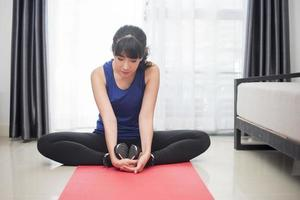 Beautiful Young sporty woman stretching at home photo