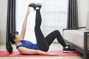 Beautiful Young sporty woman exercising at home photo