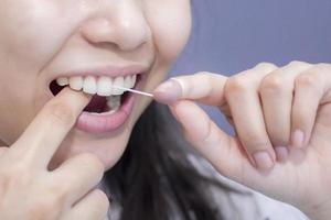 Smiling women use dental floss white healthy teeth photo