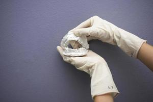 Dentist hand with plaster model photo