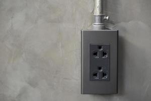 Electricity plug on industrial concrete wall background photo