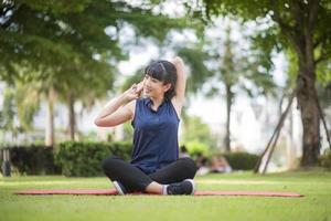 Beautiful yoga woman on green park photo