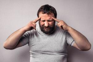 Frustrated bearded man touching his head with hands photo