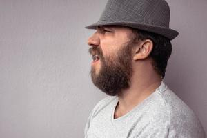 Side portrait of a bearded man shouting photo