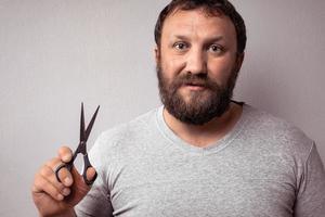 Hombre guapo con barba en camiseta gris con tijeras sobre fondo gris. foto