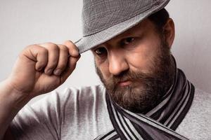 Bearded young hipster man wearing gray hat and scarf photo