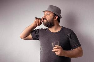 apuesto hombre barbudo con camiseta gris y sombrero bebiendo un licor fuerte foto