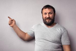 Happy bearded man in gray t-shirt looking at camera photo