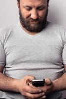 Bearded man in gray t-shirt holding mobile phone photo
