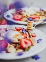 cereal para panqueques, comida de moda. mini tortitas de cereales con mantequilla, miel y fresas. foto
