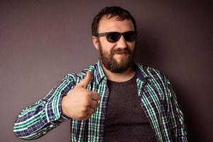 apuesto hombre barbudo hipster con gafas de sol y camisa mostrando el pulgar hacia arriba foto