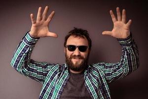 guapo, hipster, hombre barbudo, con, gafas de sol, y, camisa, con, manos arriba foto
