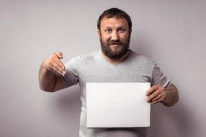 Bearded man in gray t-shirt showing blank white poster photo