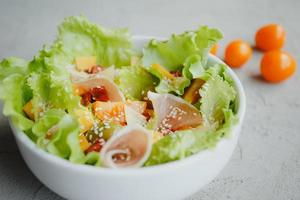 Fresh salad of lettuce, cherry tomatoes, olives, sun-dried tomatoes, Parma ham, cheddar cheese, parmesan, olive oil and sesame. Healthy eating concept. photo