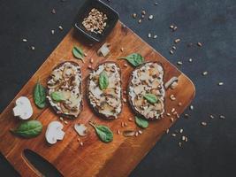 Tasty fresh bruschetta with mushrooms, spinach, garlic, cream cheese and pine nuts, on a wooden board, on a dark background. photo