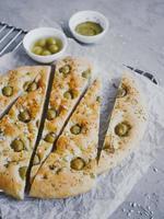 pan focaccia tradicional italiano con aceitunas, romero, sal y aceite de oliva. focaccia casera. foto