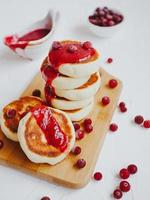 tortitas caseras de requesón o syrniki con mermelada de arándanos. foto