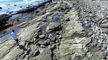 tracking shot van een jonge man die loopt op een rotsachtige kustlijn van het oceaanstrand. video