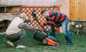 Young mature adult helping senior male with gardening work photo