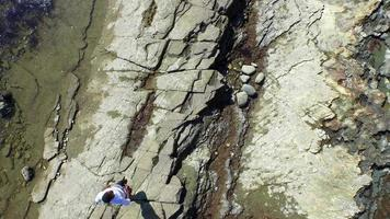 Aerial shot of young man running on a scenic rocky beach coastline. video