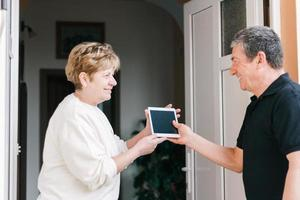 Women greeting men at doorway with electronic gadget purchase with online order photo