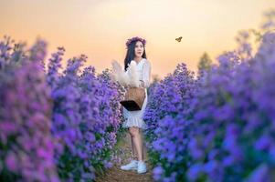 A woman watching flowers in a flower field with butterflies in the evening, orange light. photo