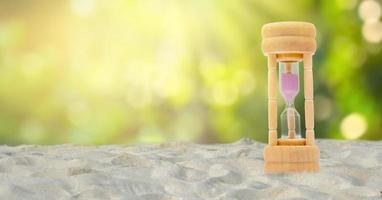 Reloj de arena sobre un fondo de arena blanca, fondo verde natural, concepto de tiempo foto