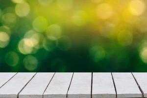 fondo verde natural con enfoque selectivo. el fondo verde tiene una hoja de bokeh y pasto sobre un piso de madera blanca. foto