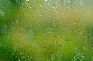 Gotas de agua de textura sobre el vidrio verde foto