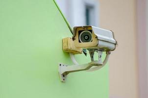 Cámara de circuito cerrado de televisión de plata en la pared verde, cámara de circuito cerrado de televisión sobre fondo verde foto