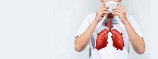 Las personas que usan una máscara con un pulmón adherido al virus corona están tosiendo sobre un fondo blanco. foto